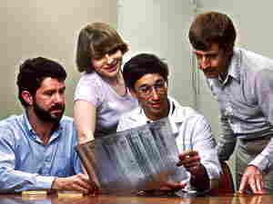 quattro scienziati al lavoro sull'elettroforesi del DNA nei laboatori NCI nel 1987